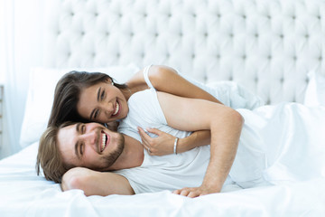 Young happy couple lying together in bed.