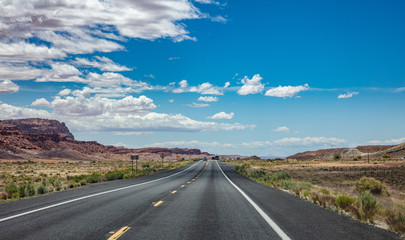 Long highway in the american desert, blue cloudy sky background