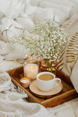 Wooden tray of coffee and candles with flowers on bed. White bedding sheets with striped blanket and pillow. Breakfast in bed. Hygge concept.