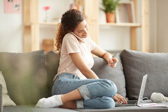 Content modern young woman in casual outfit sitting on sofa and using laptop while making order online and calling website operator