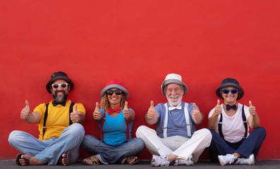 Smiling group of four people sitting against a red wall enjoying friendship gesturing ok with hands. Relaxed and positive moment. Dressed with colorful caps, bow ties and suspenders