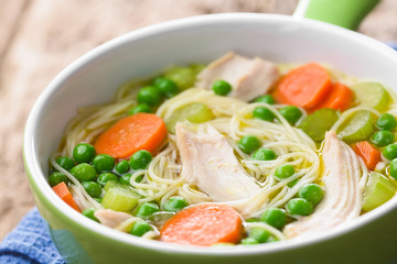 Fresh homemade chicken noodle soup with carrot, peas and celery in green soup bowl (Selective Focus, Focus in the middle of the soup)