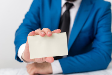 Man holds empty paper with copy space in front of him. White space for advertising message.