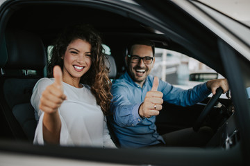 Happy middle age couple enjoying while choosing and buying new car at showroom. Fototapete
