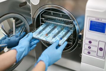 Dentist is loading dental probes into sterilize machine