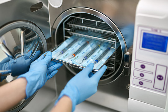 Dentist is loading dental probes into sterilize machine