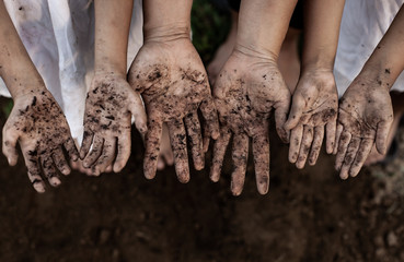 Family parent and children showing dirty hands after planting the tree together in the garden Fototapete