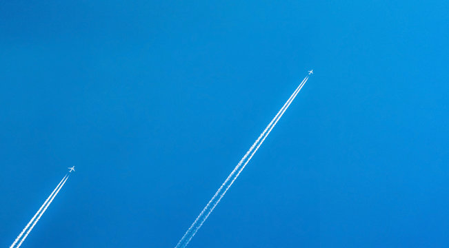 Airplane with white condensation tracks. Jet plane on clear blue sky with vapor trail. Travel by airplane concept. Trails of exhaust gas from airplane engine. Aircraft with white stripes.
