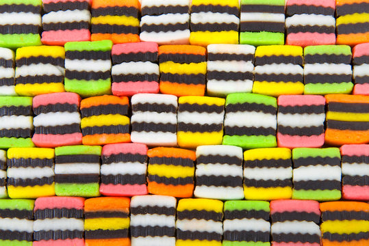 Background of bright colorful licorice candy squares alternating colors.