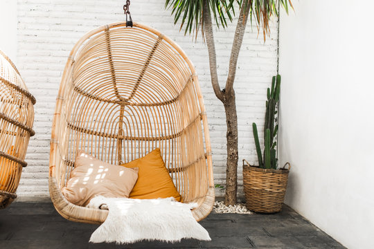 Wicker rattan hanging chair in loft cafe. Eco friendly furniture style and concept. Orange pillows and soft fur on chair. Hipster cafe in mexican style with cactus and palm.