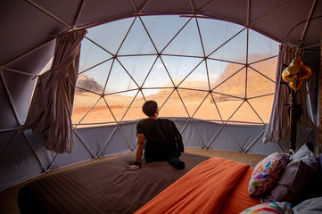 Fototapeta Asian tourist man sitting on the bed in dome tent looking outside at Wadi Rum desert, famous natural attraction in Jordan. Travel Middle east concept
