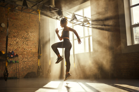Always in good shape Full length of athletic woman in black sport clothing exercising in professional gym.
