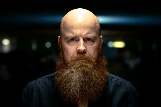 Bearded man with shaved head staring at the camera