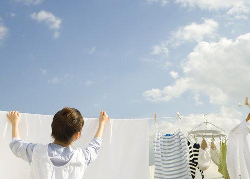青空の下で洗濯物を干す女性の後姿