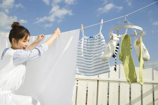 青空の下で洗濯物を干す女性