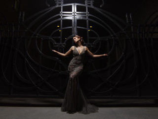 Passionate and attractive smartly dressed young woman in an expressive sparkling evening dress is posing near the big black wrought iron gate at night. Smart well-dressed glamour lady