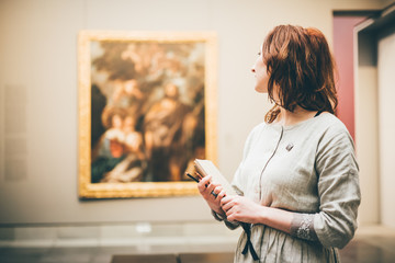 Young woman sketching in Museum. Woman holding the notepad and thinking.