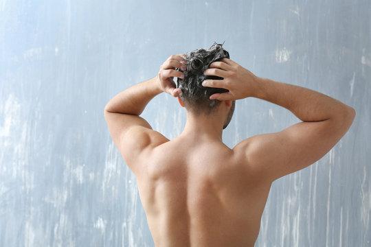 Handsome man washing hair on grey background