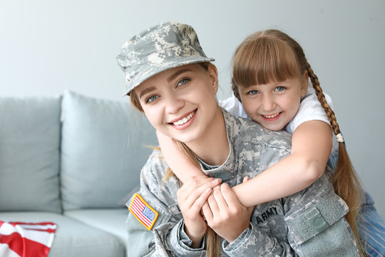 Happy female soldier with her daughter at home