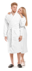Wall Mural - Happy young couple in bathrobes on white background