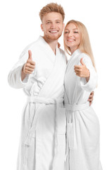 Wall Mural - Happy young couple in bathrobes showing thumb-up on white background