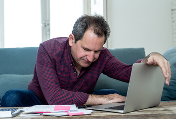 Upset middle aged man stressed about credit card debts and payments not happy accounting finances