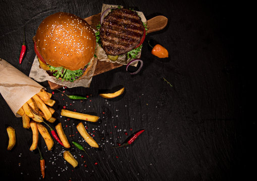Top view of home made tasty burgers on black stone table.
