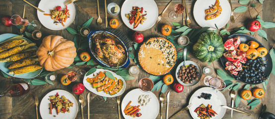 Thanksgiving, Friendsgiving holiday celebration. Flat-lay different meals at Thanksgiving Day table with turkey, pumpkin pie, roasted vegetables, fruit, rose wine, top view