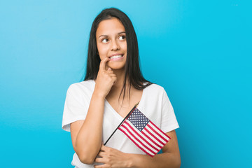 Young hispanic woman holding a united states flag relaxed thinking about something looking at a copy space.