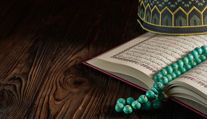 Open Quran book with rosary beads and kopiah hat for muslims on wooden table