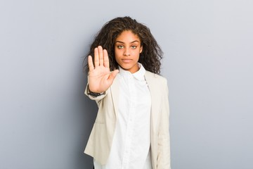 Young african american business woman standing with outstretched hand showing stop sign, preventing you.
