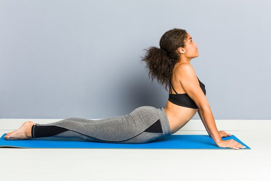 Young african american sporty woman practicing yoga lying using a mat