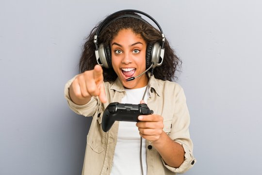 Young african american woman using headphones and game controller