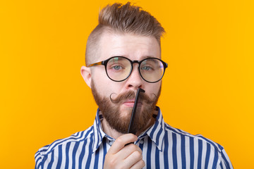 Portrait of a funny handsome young male hipster with a mustache and a beard combing his mustache on a yellow background. The concept of barbershop and beauty.