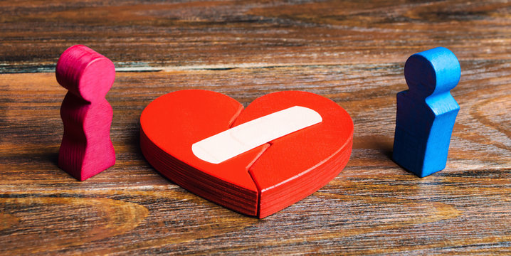 A red heart with a plaster and couple in lovers. Renewal of the relationship. Family psychotherapist services. Reconciliation. Saving the family. Search for compromises. Dispute resolution