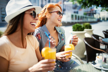 Friends having a great time in cafe. Women smiling and drinking juice and enjoying together Wall mural