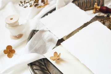 Winter, fall styled wedding, birthday table composition. Stationery mockup scene. Closeup of greeting cards, envelope, dry hydrangea flowers and ribbon on old vintage silver tray. Selective focus.