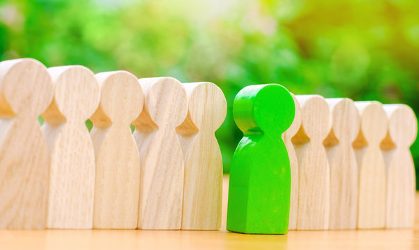 Wooden figures of people. The green man comes out with a team of workers. The concept of choosing a new leader. Choice of person. Hiring and recruiting. Talented employee. Demote. Selective focus