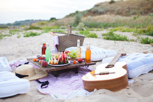 Picnic on the beach at sunset in the style boho, food and drink conception