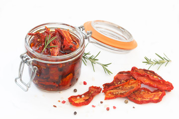 Sun dried tomatoes with herbs and spices in glass jar on white background. Healthy food ingedients for delicous cooking.