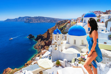 Woman in hat at beautiful Oia town of Santorini island in Greece Wall mural