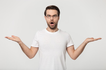 Shocked guy stretched open palms posing isolated on grey background