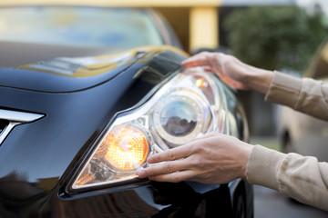 Hand holding headlight of darkcar