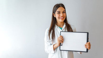 Happy doctor holding empty blank in hands. Female doctor showing a clipboard with blank paper. Close-up of a female doctor with lab coat and holding blank clipboard