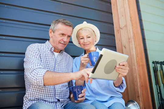 Portrait of contemporary mature couple using digital tablet while sitting on house porch, copy space