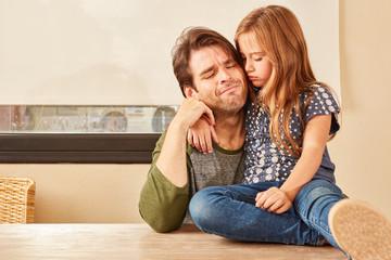 Verzweifelter Vater wird von seiner Tochter getröstet