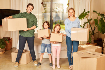 Eltern und zwei Kinder mit Umzugskartons