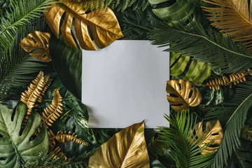 Creative nature background. Gold and green tropical palm leaves. Minimal summer abstract jungle or forest pattern. White paper frame copy space.