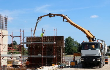 Cement mixer truck at work with its pump, during the build of the new palace first walls in the construction site