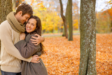 love, relationship, family and people concept - smiling couple hugging in autumn park